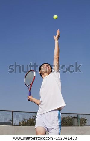 Adult men serving the tennis ball - stock photo