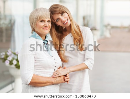 Adult mother and daughter standing at the large glass case holding hands. They are dressed in white dresses. - stock photo
