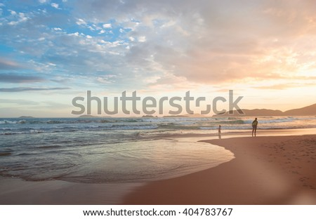 Adult people walking on the beach on sunny day  Men women and children enjoying a summer day in twilight on coastline, image for travel business concept, blog, magazine. Toned filter lens flare effect - stock photo