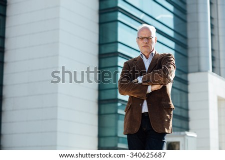 adult person with gray hair and eyeglasses elegant dressed standing outside in front of an office building - stock photo