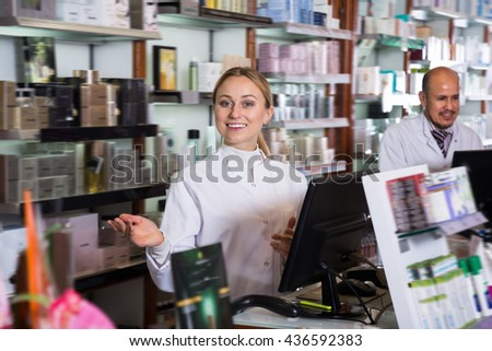 Adult pharmacists wearing white coats standing next to shelves with medicine - stock photo