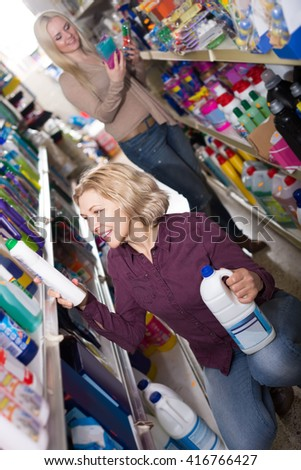 Adult positive women in good spirits selecting detergents in the store - stock photo