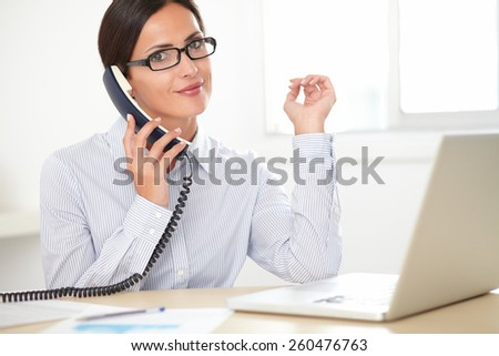 Adult secretary with glasses talking on the phone while smiling in her office - stock photo