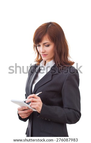 adult serious female in black suit makes some notes in notepad, isolated on white - stock photo