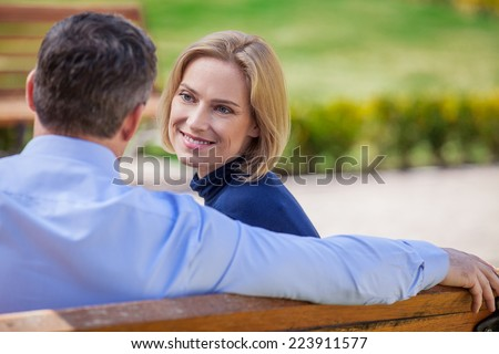 Adult smiling couple looking on each other sitting on bench. beautiful elegant mid age couple daydreaming outdoors - stock photo