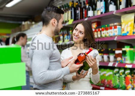 Adult smiling european shoppers choosing bottle of wine at liquor store - stock photo