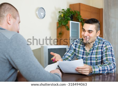 Adult smiling man helping friend to fill banking document at home