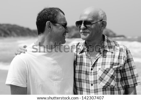 adult son and father walking together on the beach - stock photo