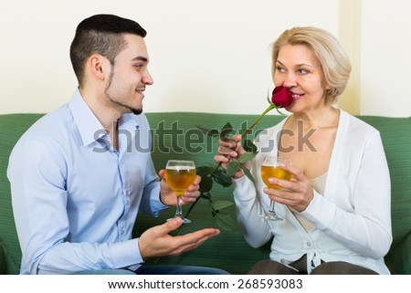 Adult son congratulating smiling mother and proposing a toast. Focus on guy - stock photo