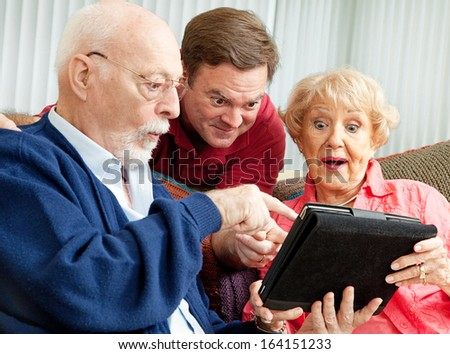 Adult son enjoys showing his parents how to use the new Tablet PC he gave them as a holiday gift.   - stock photo