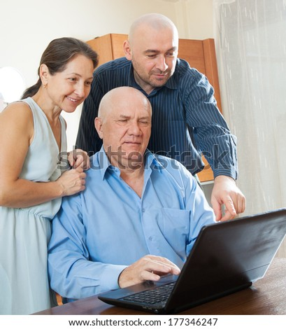 Adult son halping his perents with laptop - stock photo