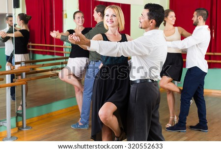 adult spanish men and women enjoying of tango in class