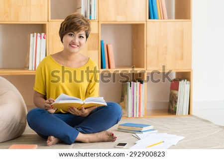 Adult student with books and papers studying at home - stock photo