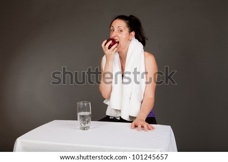 Adult sweating woman with towel after a workout eating an apple with a glass of water - stock photo