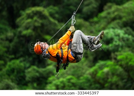 Adult Tourist On Zip Line Dressed In Orange Against Green Background - stock photo