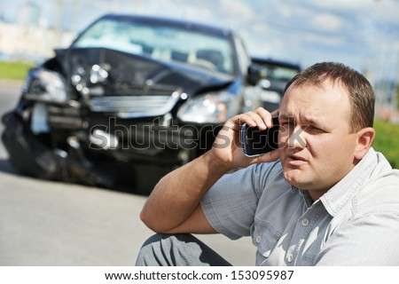 Adult upset driver man discussing on mobile phone in front of automobile crash car collision accident in city road - stock photo