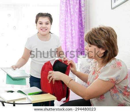 Adult woman helping  teenager to learn   lessons at home. - stock photo