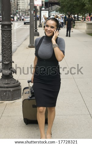 Adult woman in black outfit walking down the street on a cell phone on a sunny day - stock photo
