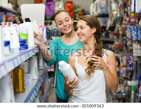 Adult woman in good spirits selecting a shampoo at the store  - stock photo