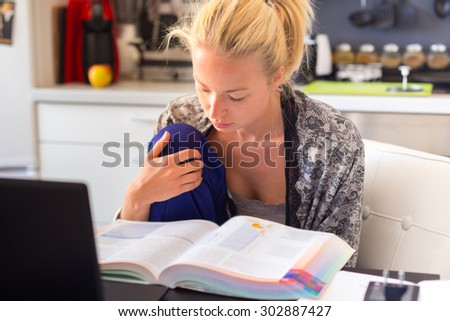 Adult woman in her casual home clothing working and studying remotely from her small flat in the morning. Home kitchen in the background. Great flexibility of web-based courses and study programmes. - stock photo
