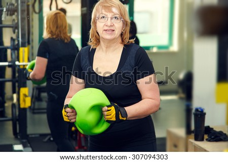 Adult woman is engaged in a sports hall. Toned image. Woman holding a dumbbell for fitness. Sporting parents. Sports and fitness a lifestyle in old age. Pretty mature woman, she client fitness club - stock photo