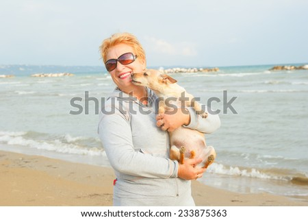 Adult woman is holding her dog. Retired woman standing on the shore of the sea or ocean. Old woman spends time with his dog on the background of the sea. Walking the dog on the beach. Tourism. Dog. - stock photo