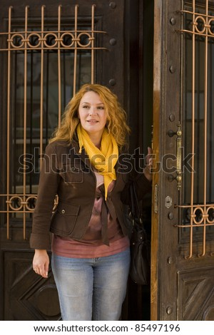 adult woman leaves the building opened the door - stock photo
