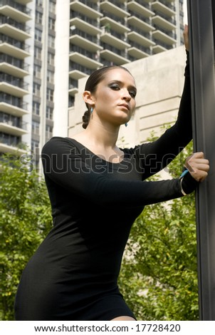 Adult woman looking at camera while standing with arms against wall on a sunny day - stock photo