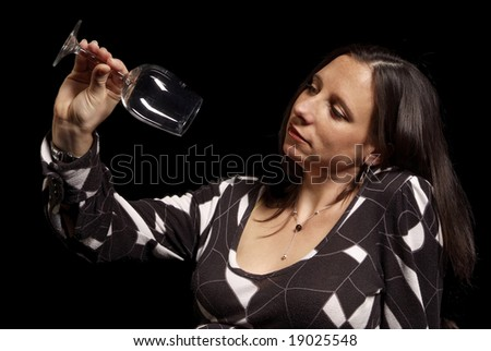 adult woman looks serious at empty wine glass - stock photo