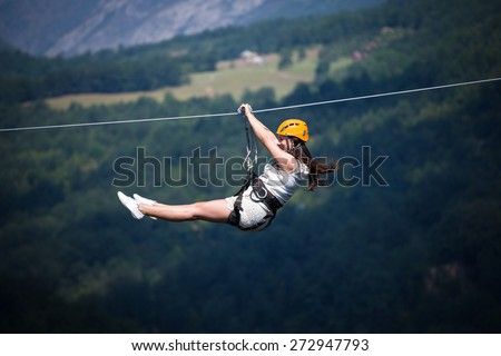 Adult woman on zip line - stock photo