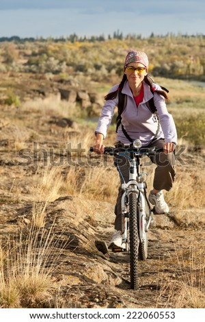 Adult woman pedaling on a mountain bike on off-road - stock photo