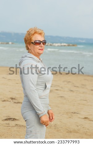 Adult woman walking on the sea beach. A walk in the fresh sea air. Sea, beach, walk, ocean, fresh air, health - concept of the modern lifestyle of the old woman on a pension. Vacation and do the walk. - stock photo