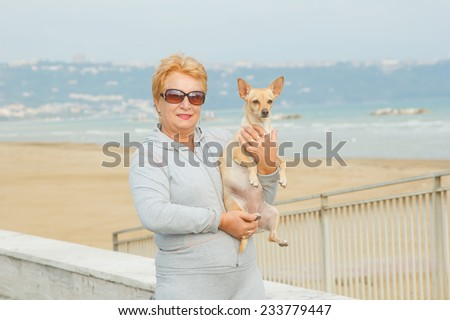 Adult woman walking with a dog on a sea beach. Walking with a pet. Dog - a friend of pensioners. Beach, sea, animals, walk, ocean, fresh air, resort - the concept of lifestyle old woman retired. - stock photo