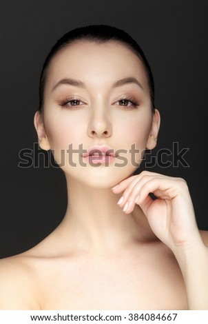 Adult woman with beautiful face. Skin care concept. Portrait of beautiful young brunette girl with clean face. Touching her face. Haughty look. - stock photo