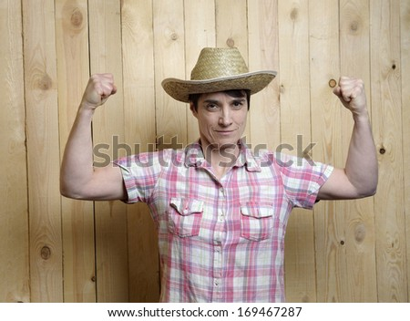 adult woman with cowboy hat showing stung muscles - stock photo