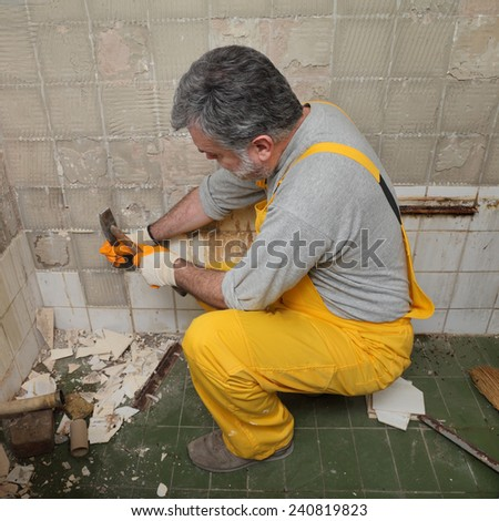 Adult worker remove, demolish old tiles in a bathroom with hammer and chisel - stock photo