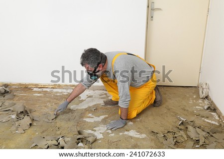 Adult worker with protective mask remove glue and rubber with putty knife from floor - stock photo