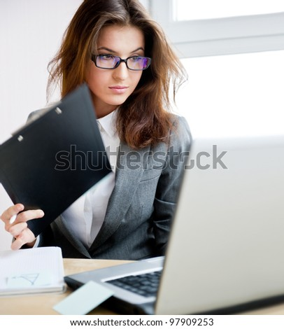 Adult young pretty business woman working at her office. She is very busy and hot. - stock photo