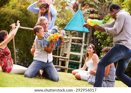 Adults and kids having fun with water pistols in a garden - stock photo