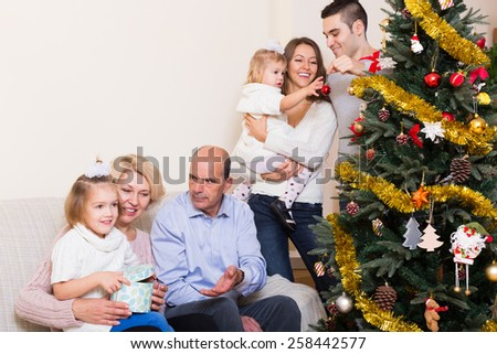 Adults and kids helping grand parent to set Xmas tree  - stock photo