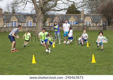 Adults on grassed area with school children supervising a football training session, Everyone can be seen running around cones. School building can be seen in the background. - stock photo