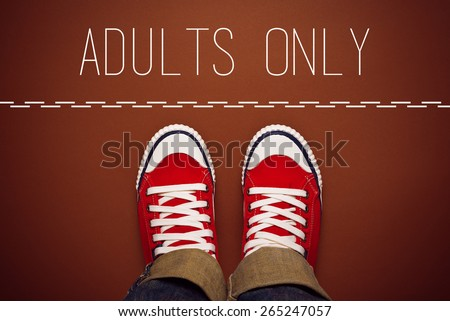 Adults Only Concept, Young Teenage Person in Red Sneakers Standing at Dividing Line of Restricted Area, top view - stock photo