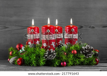 Advent wreath or crown with four red candles on wooden background. - stock photo