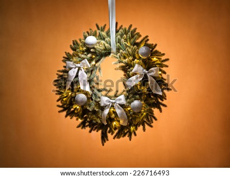 Advent wreath over beige background with silver ribbon - stock photo