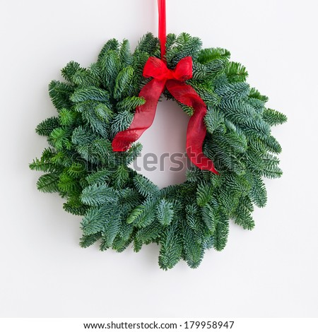 Advent wreath with red ribbon over a bright wall - stock photo