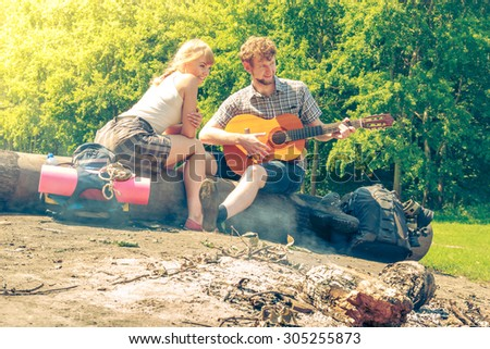 Adventure, tourism, enjoying summer time together - young couple tourists having fun playing guitar in camping outdoor - stock photo