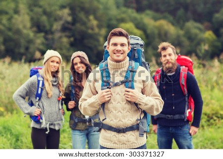 adventure, travel, tourism, hike and people concept - group of smiling friends standing with backpacks - stock photo