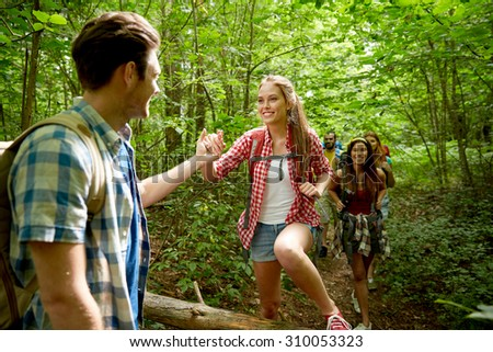 adventure, travel, tourism, hike and people concept - group of smiling friends walking with backpacks and climbing over fallen tree trunk in woods - stock photo