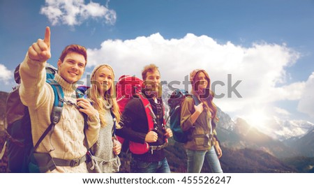 adventure, travel, tourism, hike and people concept - group of smiling friends walking with backpacks over alpine mountains and sky background - stock photo
