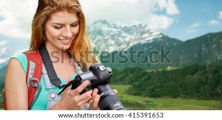adventure, travel, tourism, hike and people concept - happy young woman with backpack and camera photographing over alps mountains background - stock photo
